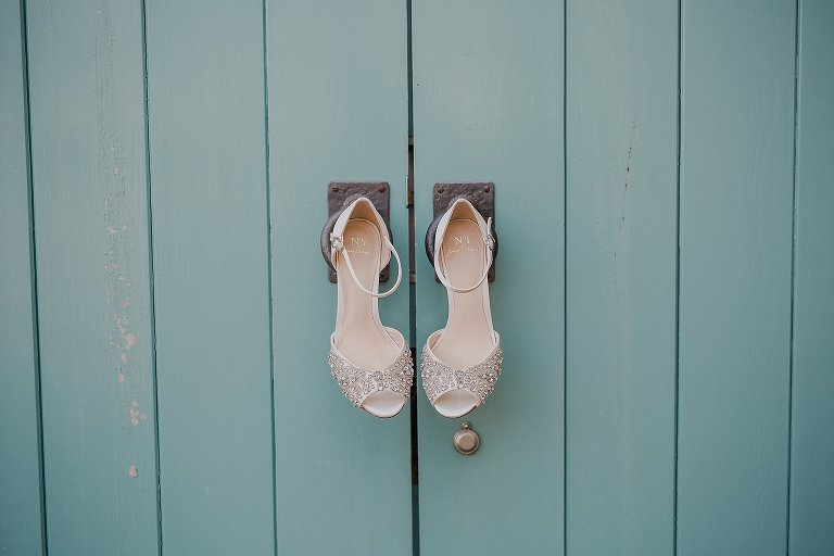 Bridal wedding shoes hung on blue door