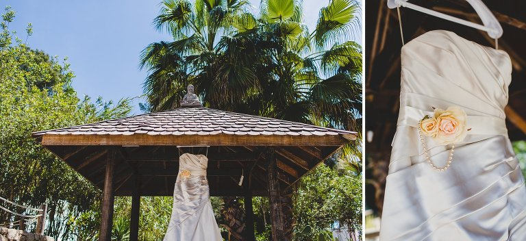 Wedding dress hung outside under palm trees in Ibiza