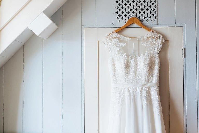 Wedding dress hung on door of cottage Alnwick