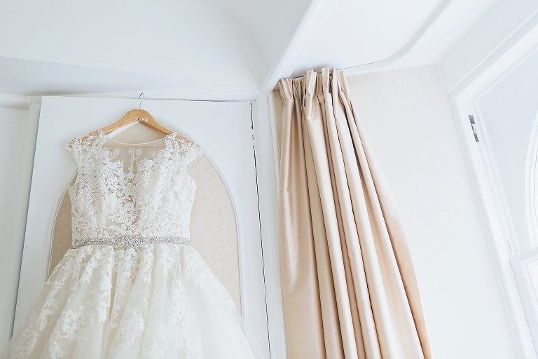 Short fit and flare wedding dress hung on wardrobe
