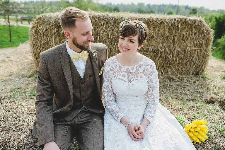 Bride and groom sitting on a hay bale