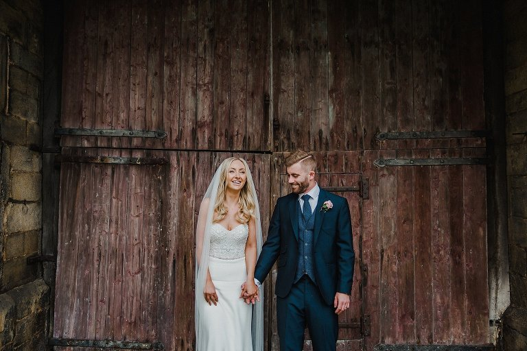 Bride and groom portrait in front of barn doors, East Riddlesden Hall