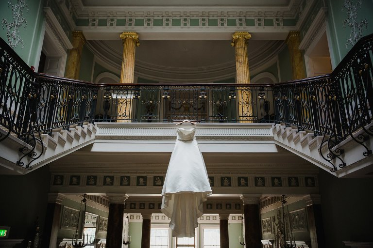 Wedding dress hanging from staircase Sledmere House