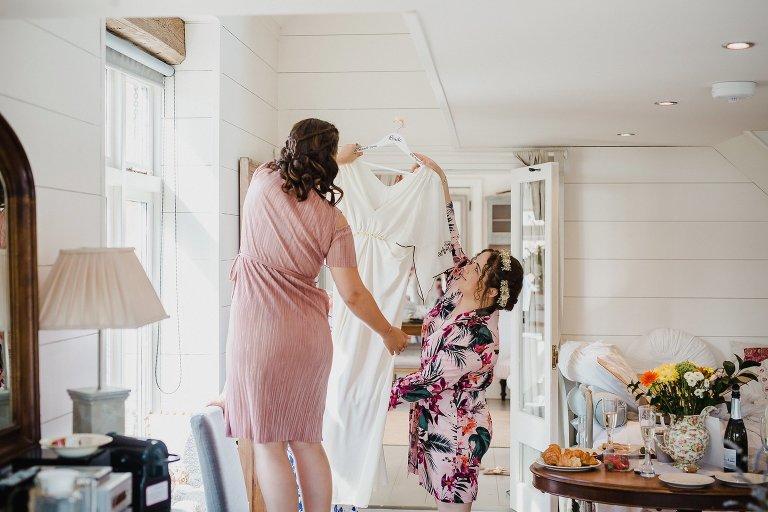 Bridal preparations bride getting into wedding dress