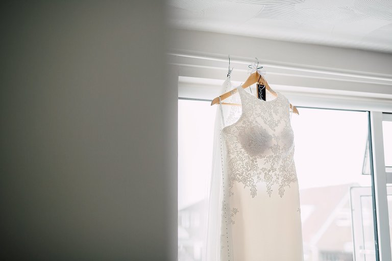 Brides wedding dress hung in the window